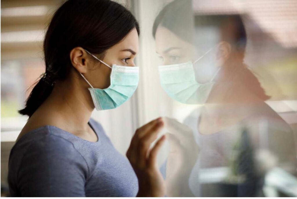 Woman with mask looking through window